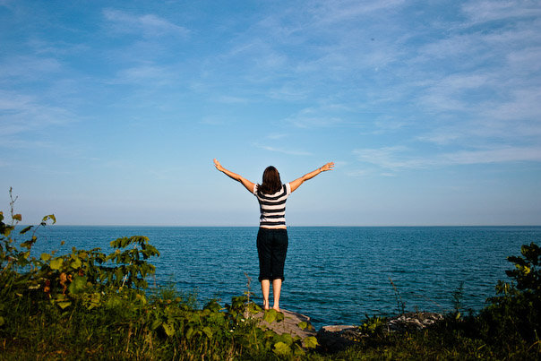 Heather Luxion, arms outstretched, looking over Lake Michigan